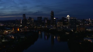 DX0002_111_001 - 5.7K stock footage aerial video ascend over Lady Bird Lake, focus on the waterfront skyline at twilight in Downtown Austin, Texas