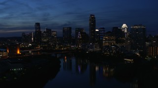 DX0002_111_002 - 5.7K stock footage aerial video follow Lady Bird Lake, focus on the waterfront skyline at twilight in Downtown Austin, Texas
