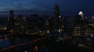 DX0002_111_004 - 5.7K stock footage aerial video fly away from Austonian and waterfront skyline, seen from Lady Bird Lake at twilight in Downtown Austin, Texas