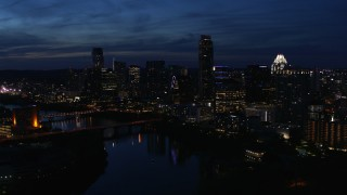 DX0002_111_005 - 5.7K stock footage aerial video a reverse view of waterfront skyline, seen from Lady Bird Lake at twilight in Downtown Austin, Texas