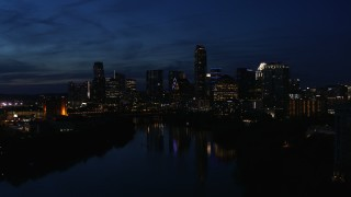 DX0002_111_009 - 5.7K stock footage aerial video slowly passing waterfront skyline on the shore of Lady Bird Lake at twilight in Downtown Austin, Texas