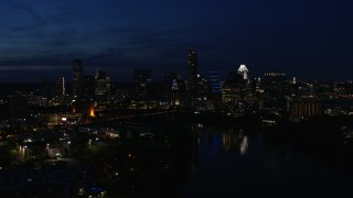 DX0002_111_010 - 5.7K stock footage aerial video ascend and flyby waterfront skyline on the shore of Lady Bird Lake at twilight in Downtown Austin, Texas
