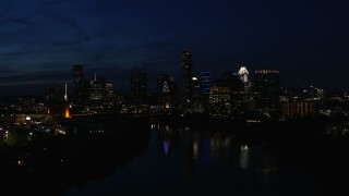 DX0002_111_013 - 5.7K stock footage aerial video slowly flyby city's waterfront skyline on the opposite shore of Lady Bird Lake at night in Downtown Austin, Texas