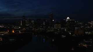 DX0002_111_014 - 5.7K stock footage aerial video slowly passing city's waterfront skyline on the opposite shore of Lady Bird Lake at night in Downtown Austin, Texas
