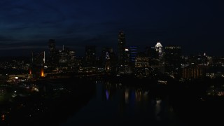 DX0002_111_015 - 5.7K stock footage aerial video of city's waterfront skyline on the opposite shore of Lady Bird Lake during descent at night in Downtown Austin, Texas