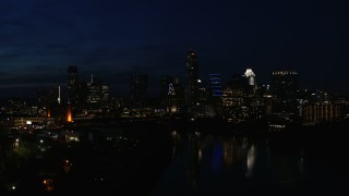 DX0002_111_016 - 5.7K stock footage aerial video approach waterfront skyline on the opposite shore of Lady Bird Lake during ascent at night in Downtown Austin, Texas