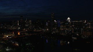 DX0002_111_017 - 5.7K stock footage aerial video fly away from waterfront skyline on the opposite shore of Lady Bird Lake at night in Downtown Austin, Texas