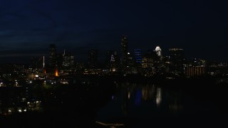 DX0002_111_018 - 5.7K stock footage aerial video descend and focus on waterfront skyline on the opposite shore of Lady Bird Lake at night in Downtown Austin, Texas
