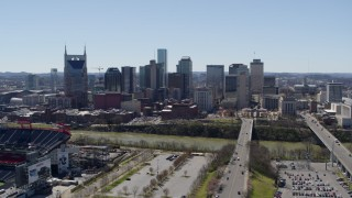 DX0002_112_008 - 5.7K stock footage aerial video focus on the city's skyline while ascending near the river in Downtown Nashville, Tennessee