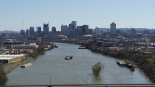 DX0002_112_020 - 5.7K stock footage aerial video a wide view of the city's skyline a barge sails the river in Downtown Nashville, Tennessee