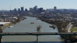 DX0002_112_027 - 5.7K stock footage aerial video flyby bridge with view of barge sailing toward city's skyline, Downtown Nashville, Tennessee