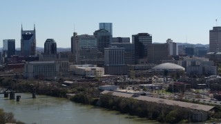DX0002_112_033 - 5.7K stock footage aerial video of crossing the river, focus on the city's skyline, Downtown Nashville, Tennessee