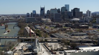 DX0002_113_008 - 5.7K stock footage aerial video a view of city's skyline while flying away from traffic on bridge over the river, Downtown Nashville, Tennessee