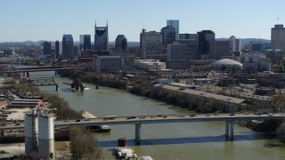 DX0002_113_012 - 5.7K stock footage aerial video of skyscrapers in the city's skyline, seen from a bridge over the river, Downtown Nashville, Tennessee