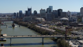 DX0002_113_013 - 5.7K stock footage aerial video flyby bridge over the river, focus on city's skyline Downtown Nashville, Tennessee
