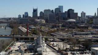DX0002_113_015 - 5.7K stock footage aerial video descend near bridge with heavy traffic, focus on city's skyline Downtown Nashville, Tennessee