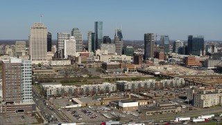 DX0002_113_021 - 5.7K stock footage aerial video descend for view of city's skyline behind apartment buildings in Downtown Nashville, Tennessee