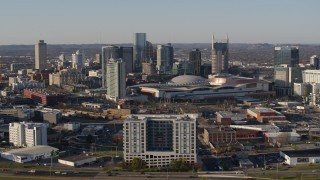 DX0002_114_020 - 5.7K stock footage aerial video ascend and flyby the city skyline behind the convention center in Downtown Nashville, Tennessee