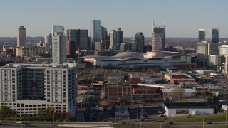 DX0002_114_022 - 5.7K stock footage aerial video fly away from the city skyline behind the convention center, descend by apartments in Downtown Nashville, Tennessee