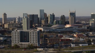DX0002_114_037 - 5.7K stock footage aerial video descend by apartment complex, focus on city's tall skyline by the convention center in Downtown Nashville, Tennessee
