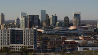 DX0002_114_038 - 5.7K stock footage aerial video ascend past apartment complex, focus on city's tall skyline by convention center in Downtown Nashville, Tennessee