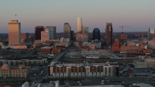 DX0002_115_009 - 5.7K stock footage aerial video descend near apartments, focus on city's skyline at sunset in Downtown Nashville, Tennessee