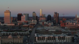 DX0002_115_012 - 5.7K stock footage aerial video ascend from apartment complex, fly away from city's skyline at sunset in Downtown Nashville, Tennessee