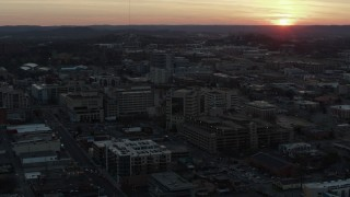 DX0002_115_015 - 5.7K stock footage aerial video ascend and fly away from hospital with view of setting sun, Nashville, Tennessee