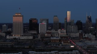 DX0002_115_026 - 5.7K stock footage aerial video flying by skyscrapers reflecting light in the city skyline at twilight in Downtown Nashville, Tennessee