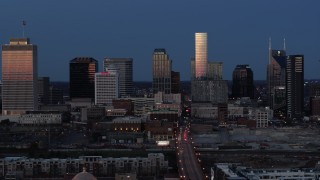 DX0002_115_027 - 5.7K stock footage aerial video descend while flying by skyscrapers reflecting light in the city skyline at twilight in Downtown Nashville, Tennessee