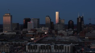 DX0002_115_028 - 5.7K stock footage aerial video passing by skyscrapers reflecting light in the city skyline at twilight in Downtown Nashville, Tennessee