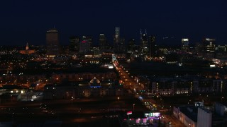 DX0002_115_051 - 5.7K stock footage aerial video following Church Street toward the city skyline at night, Downtown Nashville, Tennessee