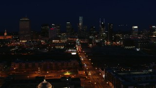 DX0002_115_052 - 5.7K stock footage aerial video fly away from the city skyline at night, reveal flashing lights on Church Street, Downtown Nashville, Tennessee