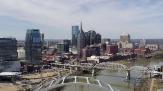 DX0002_116_002 - 5.7K stock footage aerial video fly away from and past skyscrapers, and bridge spanning the river in Downtown Nashville, Tennessee