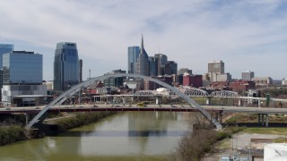 DX0002_116_005 - 5.7K stock footage aerial video reverse and then stationary view of skyscrapers seen from a bridge spanning the river in Downtown Nashville, Tennessee