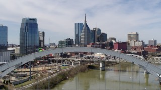 DX0002_116_006 - 5.7K stock footage aerial video fly over a bridge spanning the river to approach AT&T Building in Downtown Nashville, Tennessee