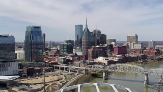 DX0002_116_007 - 5.7K stock footage aerial video of a reverse view of the AT&T Building and a bridge over the river in Downtown Nashville, Tennessee