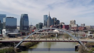 DX0002_116_008 - 5.7K stock footage aerial video descend near a bridge over the river with view of skyscrapers in Downtown Nashville, Tennessee