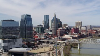 DX0002_116_012 - 5.7K stock footage aerial video of flying by skyscrapers and reveal a bridge over the river in Downtown Nashville, Tennessee