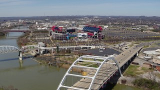 DX0002_116_021 - 5.7K stock footage aerial video of a wide orbit of Nissan Stadium, seen from near a bridge in Nashville, Tennessee