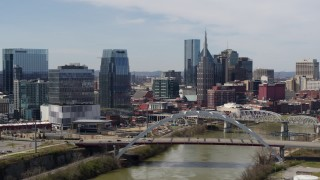 DX0002_116_025 - 5.7K stock footage aerial video of slowly flying by the river and bridge, focus on skyscrapers in Downtown Nashville, Tennessee