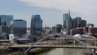 DX0002_116_028 - 5.7K stock footage aerial video fly away from river and bridge, office high-rise and skyscrapers in Downtown Nashville, Tennessee