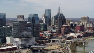 DX0002_116_030 - 5.7K stock footage aerial video flyby Cumberland River and bridge, closer view of office high-rise and skyscrapers in Downtown Nashville, Tennessee