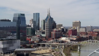 DX0002_116_034 - 5.7K stock footage aerial video ascend near bridge to focus on the AT&T Building in Downtown Nashville, Tennessee
