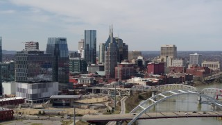 DX0002_116_037 - 5.7K stock footage aerial video of the AT&T Building seen while flying by a bridge and the river in Downtown Nashville, Tennessee