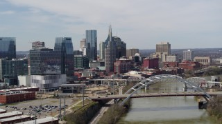 DX0002_116_038 - 5.7K stock footage aerial video of the city's tall skyscrapers and a bridge on the Cumberland River in Downtown Nashville, Tennessee