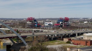 DX0002_116_045 - 5.7K stock footage aerial video reverse view of Nissan Stadium behind the bridge in Nashville, Tennessee