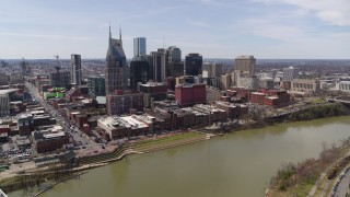 DX0002_117_006 - 5.7K stock footage aerial video reverse view of the city's riverfront skyscrapers by the Cumberland River, Downtown Nashville, Tennessee