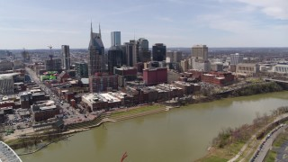 DX0002_117_008 - 5.7K stock footage aerial video wide orbit of the city's riverfront skyscrapers across the Cumberland River, Downtown Nashville, Tennessee