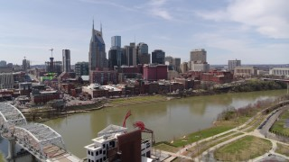 DX0002_117_009 - 5.7K stock footage aerial video orbiting city's riverfront skyscrapers across the Cumberland River, seen from pedestrian bridge, Downtown Nashville, Tennessee